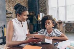 显示女孩数字式片剂的母亲 免版税库存图片