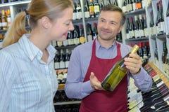 显示女性客户瓶白葡萄酒的专业斟酒服务员 免版税库存图片