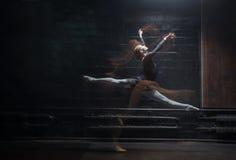 显示她在黑暗的背景的年轻女性体操运动员麻线 免版税库存照片