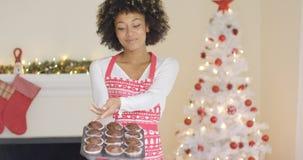 显示她的圣诞节松饼的骄傲的年轻人厨师 库存照片