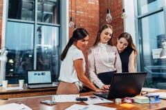 显示她的在膝上型计算机的工作的结果妇女对站立的同事在创造性的现代办公室 免版税库存照片