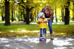 显示她的小孩儿子如何的年轻母亲乘坐一辆滑行车在秋天公园 库存图片