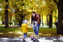 显示她的小孩儿子如何的年轻母亲乘坐一辆滑行车在秋天公园 图库摄影