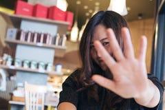 显示她的手标志的一名亚裔妇女盖她的面孔对某人说没有感到的滑稽 图库摄影