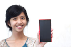 显示她的智能手机的美丽的亚裔女孩 免版税库存图片