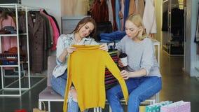 显示她的朋友的女性顾客购买了衣裳,当一起坐在精品店时 女孩被激发关于价格 股票录像