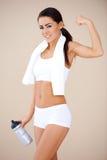显示她的肌肉的愉快的健身女孩 免版税库存照片