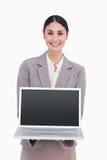 显示她的膝上型计算机的屏幕微笑的女实业家 免版税库存图片