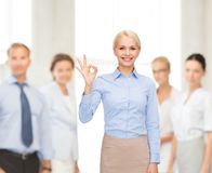 显示好标志用手的微笑的女实业家 库存图片