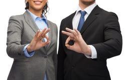 显示好标志的商人和女实业家 免版税库存图片
