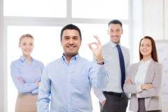 显示好标志的微笑的商人在办公室 免版税库存图片