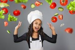 显示好标志的快乐的小女孩厨师 免版税库存图片