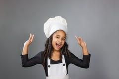 显示好标志的快乐的小女孩厨师 免版税图库摄影