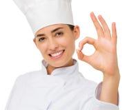 显示好标志的愉快的女性厨师 免版税库存照片
