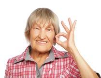 显示好标志的老愉快的妇女 免版税库存照片