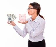 显示存钱罐和美金的女实业家 图库摄影