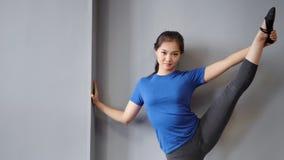 显示完善舒展的微笑的亚洲女性跳芭蕾舞者举用手举行一条的腿 股票视频