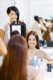 显示客户的发型美发师在镜子 库存图片