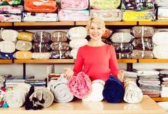 显示家庭纺织品的宽分类的愉快的资深卖主 库存照片