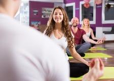 显示对学习者瑜伽姿势的教练 免版税库存图片
