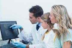 显示小女孩她的嘴X-射线的牙医和助理 免版税库存图片