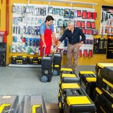 显示工具箱的推销员对顾客在商店 库存照片