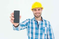 显示巧妙的电话的愉快的建筑工人 免版税库存图片