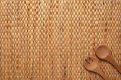 显示干凤眼兰和叉子的纹理与木匙子的placemat背景在与拷贝空间的角落 免版税库存照片