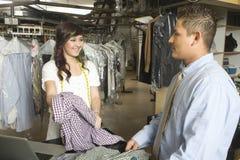 显示干洗的衣裳的所有者对顾客在柜台 免版税库存照片