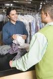 显示干洗的衬衣的所有者对顾客在柜台 免版税库存照片