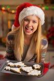 显示平底锅曲奇饼的圣诞老人帽子的少年女孩 免版税库存照片