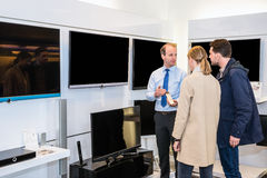 显示平面屏幕电视的推销员对夫妇在商店 库存照片