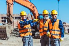 显示建造者某事的工头在建造场所通过指向他的 免版税库存照片