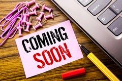显示很快来的手写的文本 在木backgrou的桃红色稠粘的便条纸写的消息未来的企业概念 免版税库存照片