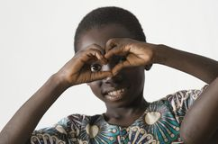 显示心脏标志用他的手的小非洲黑人孩子, 免版税库存图片