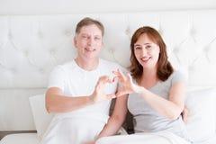 显示心脏标志的微笑的中年夫妇由胳膊在卧室 爱和家庭生活关系概念 选择聚焦 免版税库存图片