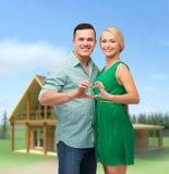 显示心脏用手的微笑的夫妇 免版税库存图片