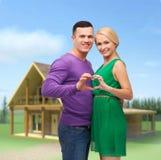 显示心脏用手的微笑的夫妇 免版税图库摄影