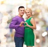 显示心脏用手的微笑的夫妇 免版税库存照片