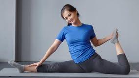 显示惊人舒展在pilates类的愉快的亚裔妇女坐席子全景 影视素材