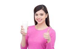 显示愉快的少妇拿着一块玻璃用牛奶和翻阅u 库存照片
