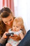 显示感兴趣婴孩照片的母亲秘密审议 免版税库存图片