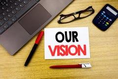 显示我们的视觉的手写的文本说明 企业在纸写的销售方针视觉的概念文字,木backg 图库摄影