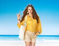 显示我爱你手势的海滩的微笑的妇女 免版税库存图片