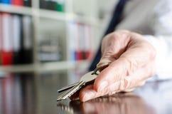 显示房子钥匙的房地产经纪商 免版税库存照片