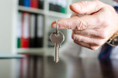 显示房子钥匙的房地产经纪商 免版税图库摄影