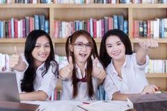 显示手势的愉快的学习者在图书馆 免版税库存照片