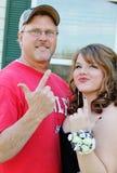 显示手指枪的爸爸对女儿正式舞会日期 免版税图库摄影