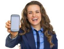 显示手机的愉快的女商人 免版税库存图片