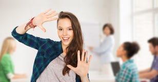 显示手的少年学生女孩在学校 免版税库存图片